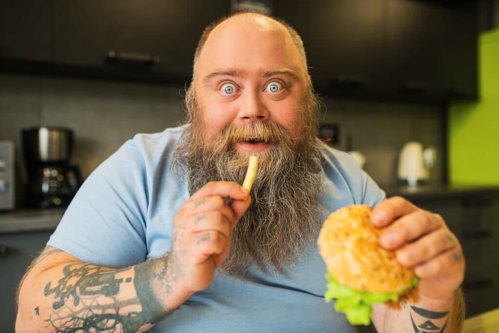 мужчина толстяк ест бургер
